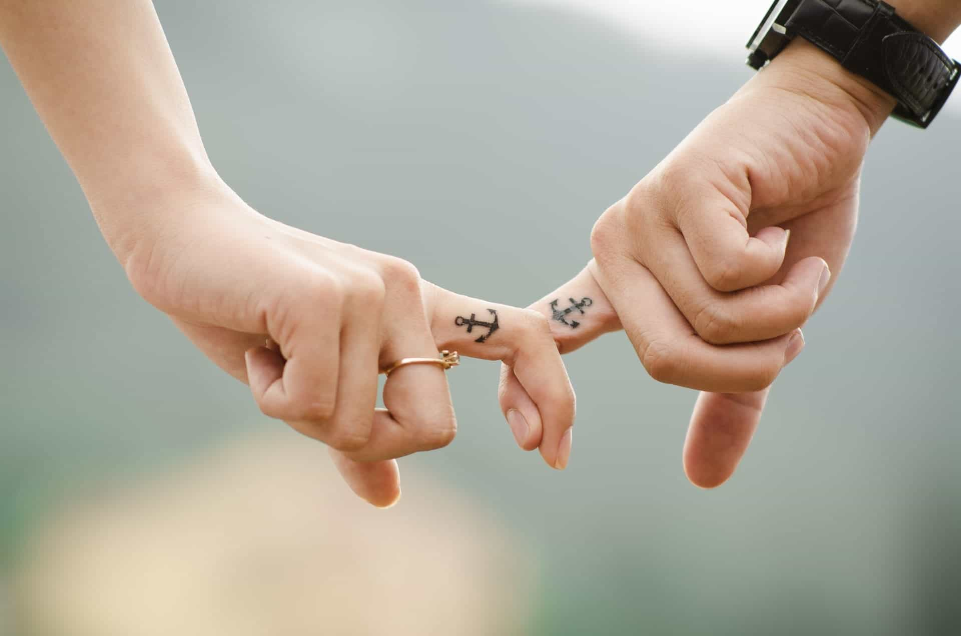 fingers holding hands with tattoos pexels-photo-38870